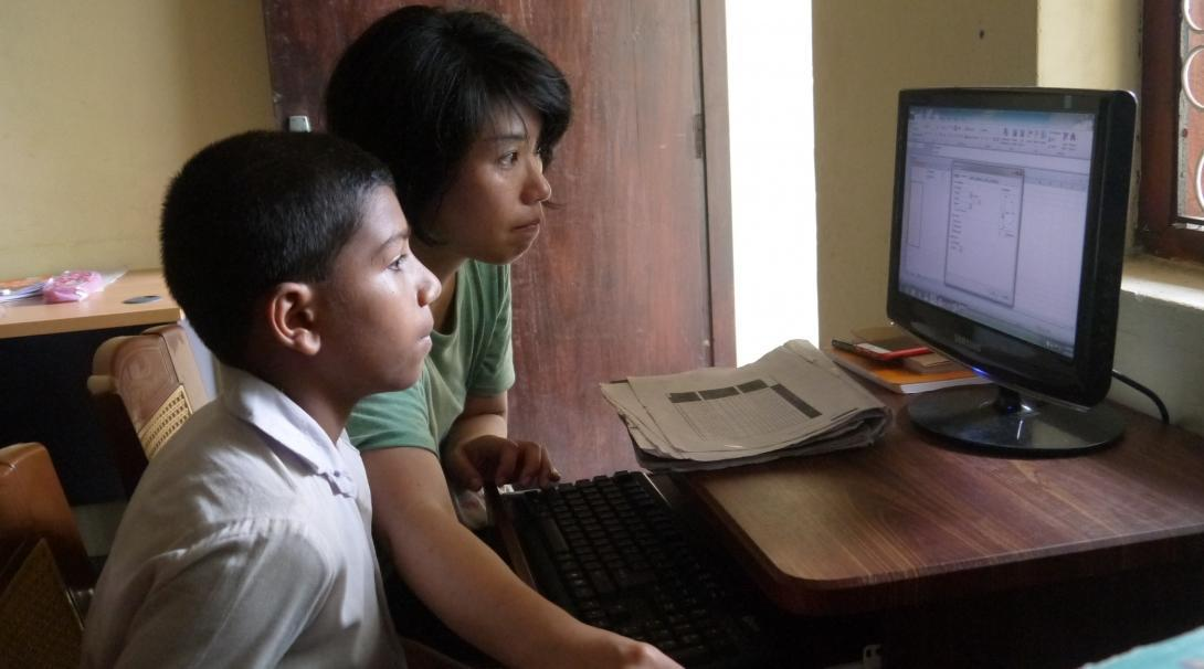 Una voluntaria ayuda a su alumno enseñándole informática básica en Sri Lanka.